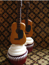 Cool cupcake with mini guitars on the top.PNG