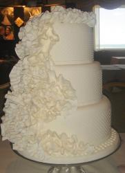 Three tier round white wedding cake with ruffles.JPG