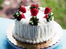Small white cream cake with fresh strawberries on top.JPG