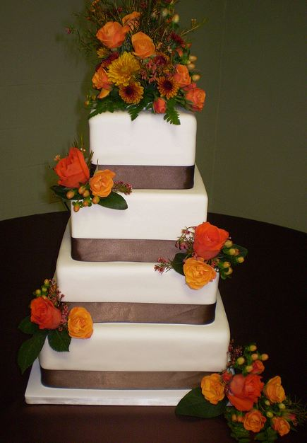 Four Tier White Wedding Cake With Brown Ribbons And Fresh FlowersJPG