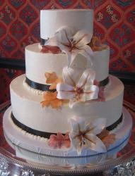 3 tier white round wedding cake with pearls and white flowers.JPG