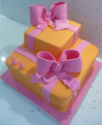 Two tier orange gift box cake with pink bowties.JPG