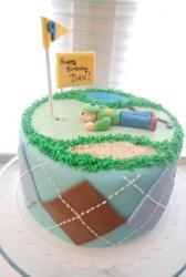 Golf theme cake with plaid pattern and golfer laying on the ground.JPG