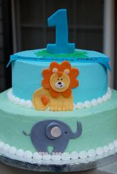 Two tier first birthday cake with lion and elephant and the number one on top.JPG