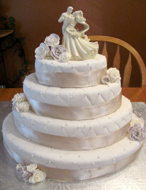 Four Tier White Round Wedding Cake With White Flowers And