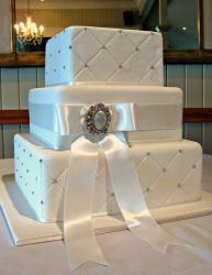 Three tier rectangular quilted white wedding cake with silver ribbon.JPG
