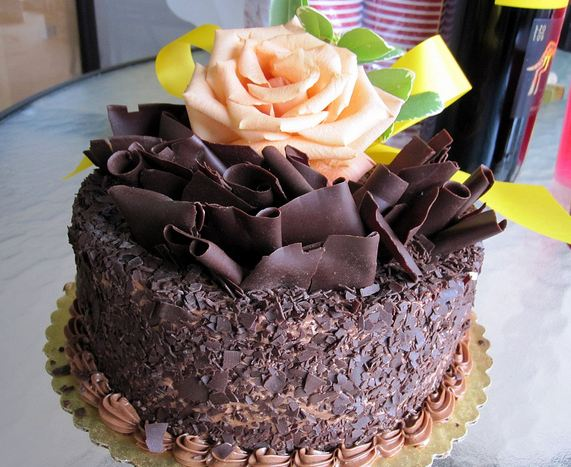 Dark chocolate cake with pink rose on top.JPG