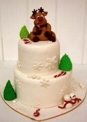 Two tier round white Christmas cake with reindeer on top.JPG