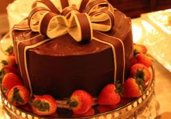 Round chocolate cake with bow and fresh strawberries surrounding.JPG