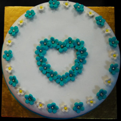 Heart sharped engagment cake with small blue and white daisy flowers.PNG