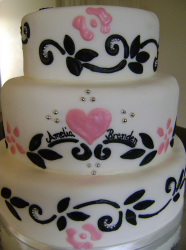 White chic engagement cake with black patterns and pink patterns and heart.PNG