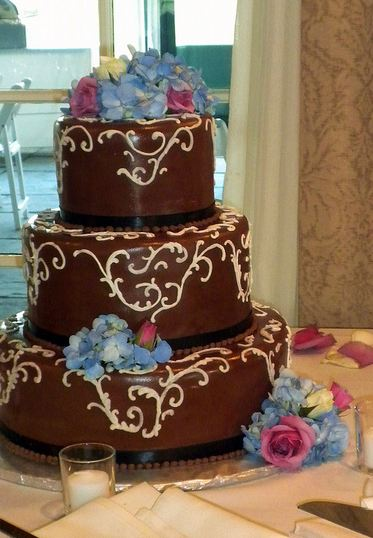 Three tier chocolate round wedding cake with blue flowers and pink roses.JPG