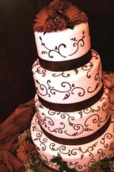 wedding cake with brown patterns and wide ribbon with flowers on top