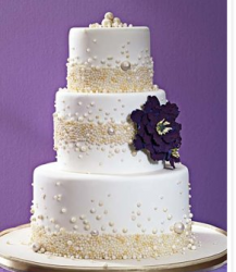 Elegant pearl wedding cake with a big dark purple flower.PNG