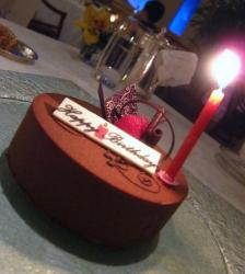 Round simple chocolate birthday cake with red candle.JPG
