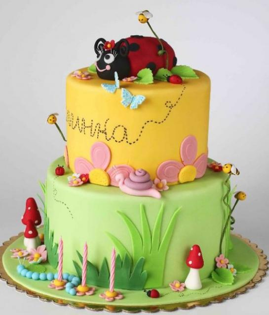 Dual tier garden theme birthday cake with big ladybug on top with mushrooms and bees.JPG