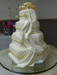 Four tier hexagonal wedding cake with gold bow and white drapes.JPG