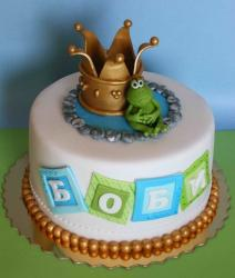 Round white cake with gold crown and frog and golden pearls.JPG