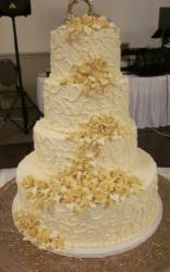 Four tier ivory wedding cake with yellow roses and gold swan toppers.JPG