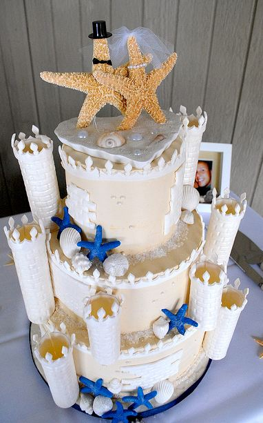 Three tier white castle theme wedding cake with star fish bride and groom toppers.JPG