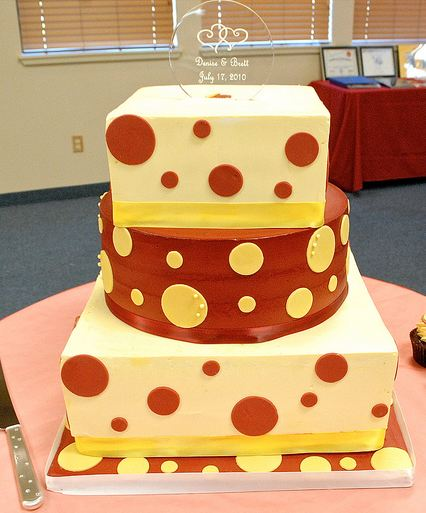 Three tier square wedding cake in white and brown with round middle tier.JPG