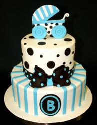 Two tier white and blue baby shower cake with black bow and baby stroller topper.JPG