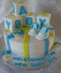 White round baby boy shower cake with baby blocks and shoes on top.JPG