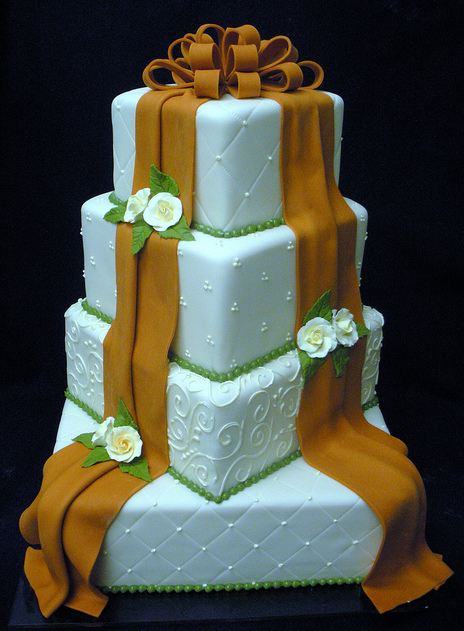 Four tier white square wedding cake with brown bow and drapes and white roses.JPG