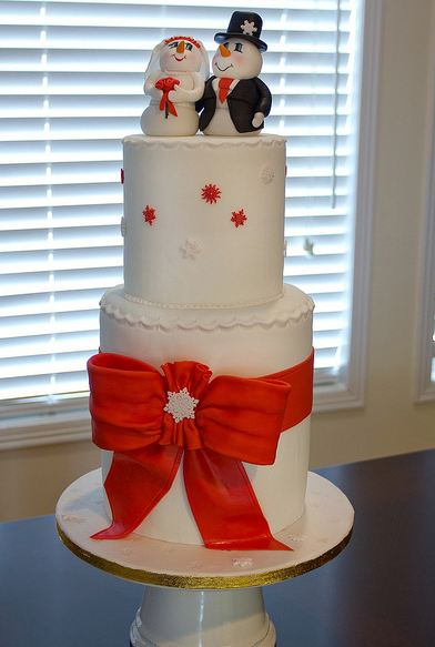 Two tier white cylindrical wedding cake with red bow and snowman and snow woman toppers.JPG