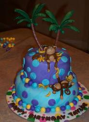 Two tier indigo and blue round island theme birthday cake with palm trees and monkeys.JPG