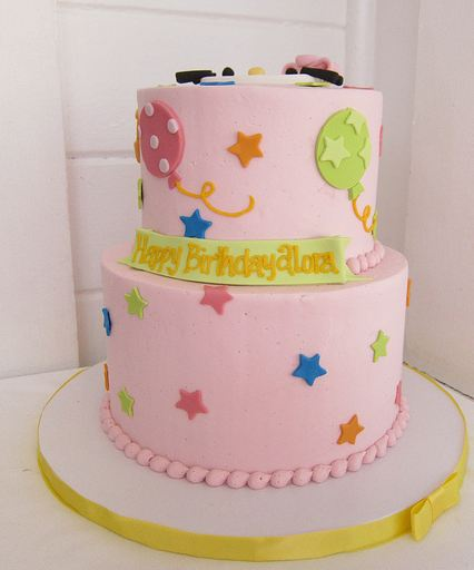 Two tier pink round birthday cake with stars and balloon decorations.