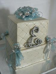 Two tier square elegant wedding cake with blue ribbons and silver monogram.JPG