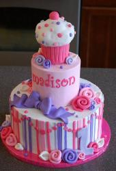 Three tier birthday cake with a girl with top tier a pink and white cupcake.JPG