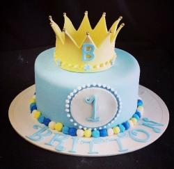 First birthday cake in blue with a gold crown on top.JPG
