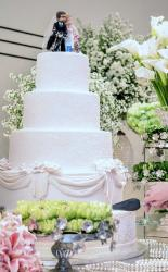 4 tier round wedding cake with Bride Groom on motorcycle topper & drapes.JPG
