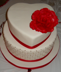 Wedding valentine theme cake in white with large red rose cake topper.PNG