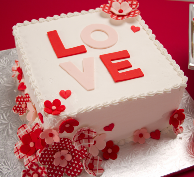 White square valentine cake with white and red flower cakes.PNG