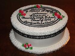 round white and black graduation cake with red flowers.jpg