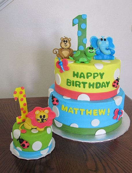 Two tier Safari theme first birthday cake with animals and matching mini cake.JPG
