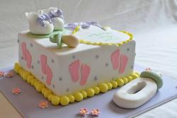 White square baby shower cake with pink footprints and boots and pacifiers.JPG