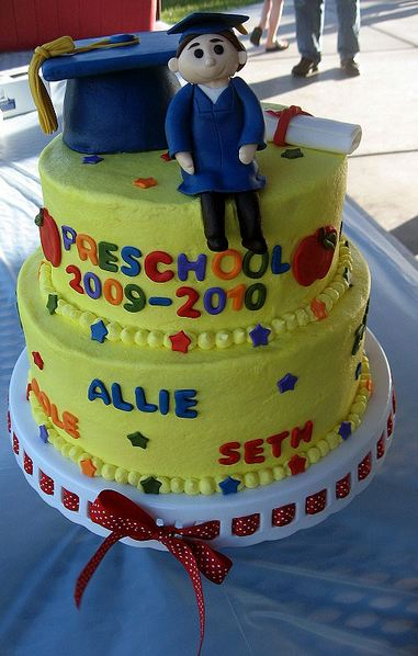Two tier yellow round graduation cake with blue cap and student on top with diplomma.JPG