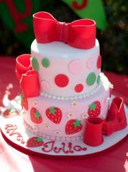Two tier light pink round cake with red bowties and strawberry art.JPG