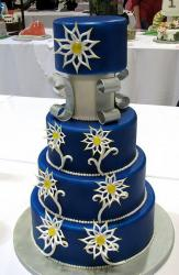 Four tier round dark blue wedding cake with white flower patterns.JPG