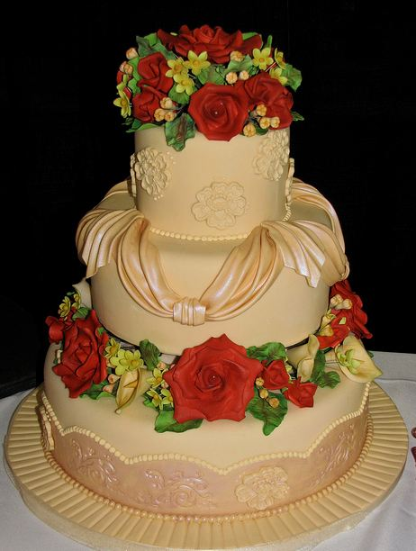 Three tier round wedding cake with drapes and fresh red roses.JPG
