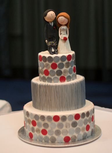 Three tier round white wedding cake with red and metallic coins and bride and groom topper.JPG