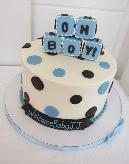 ... circular white baby shower cake w/ blue blocks at the top for baby boy