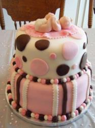 2 tier baby shower cake in pink and white with baby on top having diaper change.JPG
