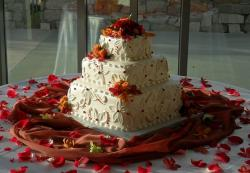 Three tier square butter cream wedding cake with orange and red flower petals.JPG