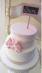 Two tier pink and white birthday cake with pink bow and sign.JPG