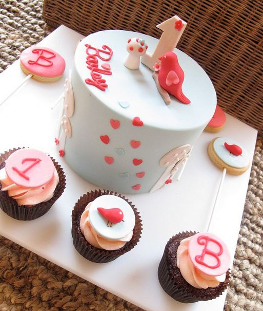 Round First Birthday Cake With Three Cupcakes For Baby